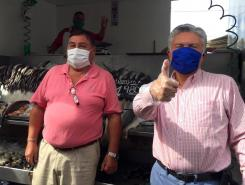 Two men standing at fish market. Both wear face masks.