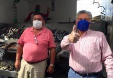 Two men standing at fish market. Both wear face masks.