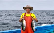 Peruvian fisher standing in a boat, holding two fish